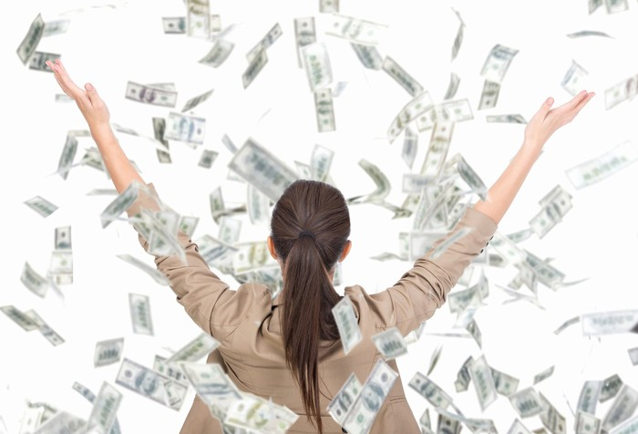 Dollar bills raining on a woman with her hands in the air