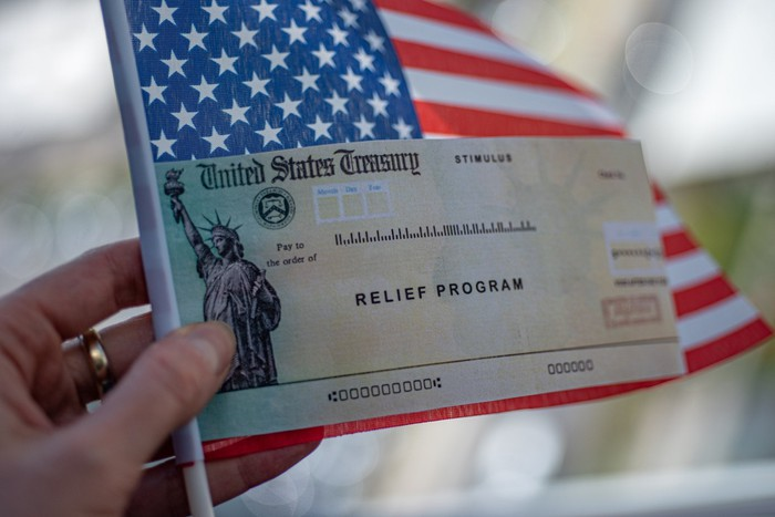 A check labeled Relief Program being held on top of an American Flag.