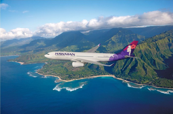 A Hawaiian Airlines plane flying over the ocean, with mountains in the background