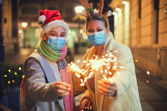 Two women in masks and Christmas headwear, holding sparklers