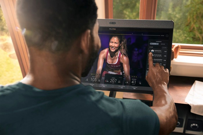 A man exercises using a Peloton Bike while watching training video.