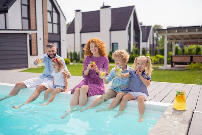 A family with their feet in a pool behind their house drinking lemonade.