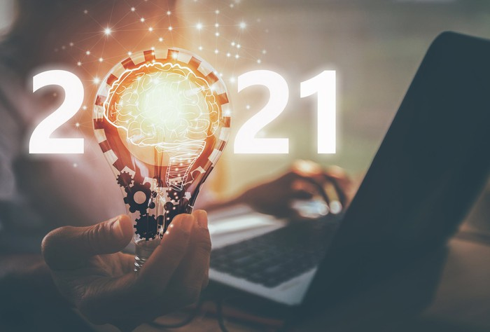 Man at laptop holds lightbulb with 2021 written across it