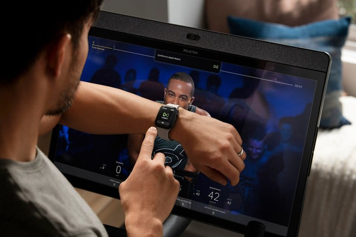 Person on Peloton bike watching screen and using watch.