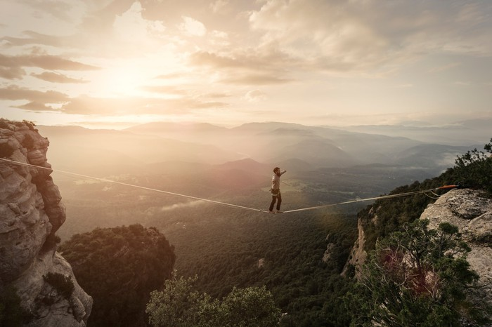 An individual walking a tightrope with mountains in the background