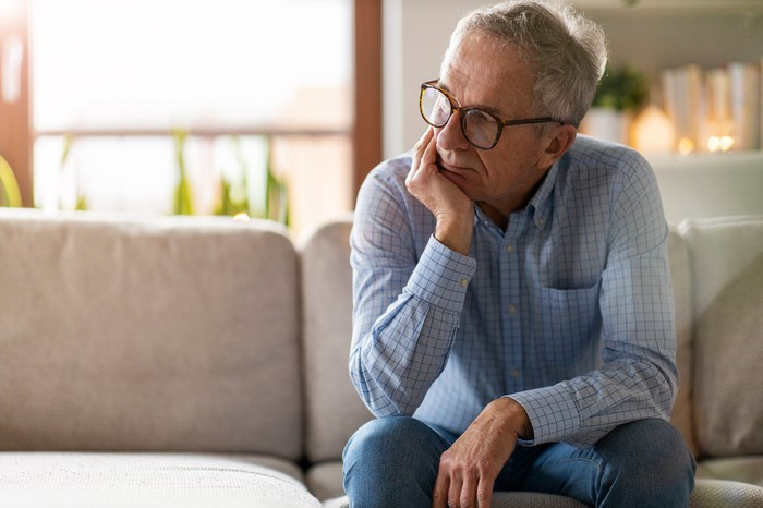 Older man sitting on couch with concerned expression