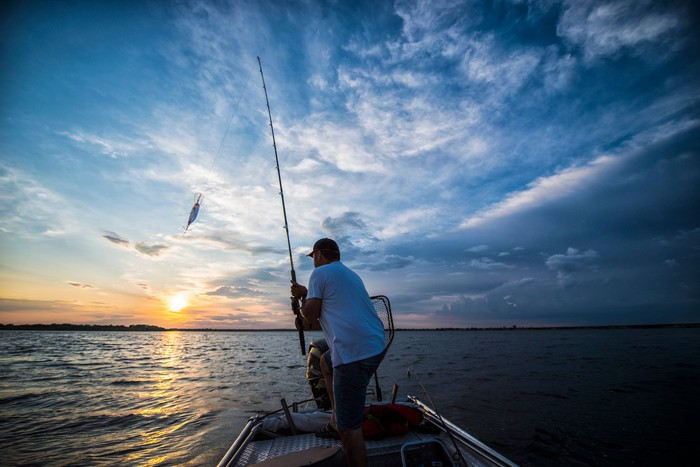 A fisherman on a small boat catching a fish from a lake at sunrise or sunset.