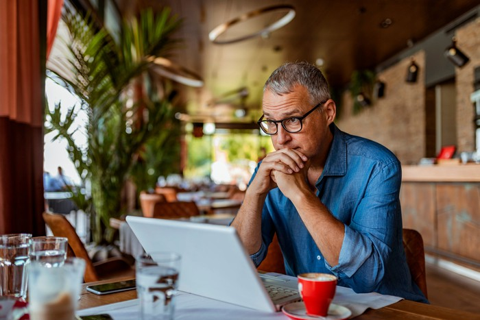 Older man sitting at laptop with serious expression