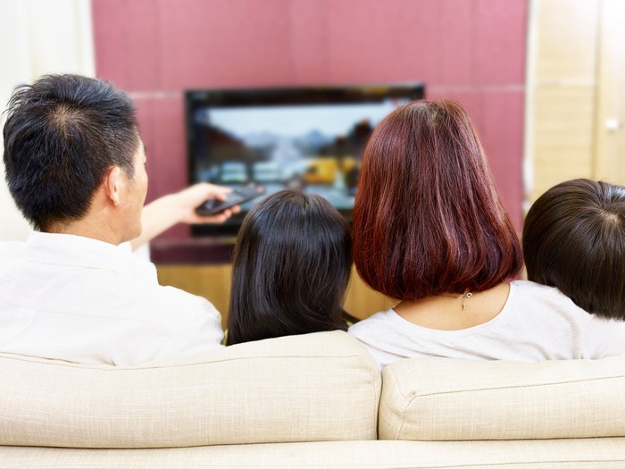 Family sitting on the couch watching television.