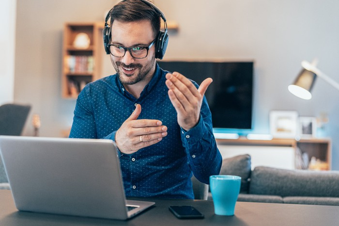 Man in headphones on video conference while at home.