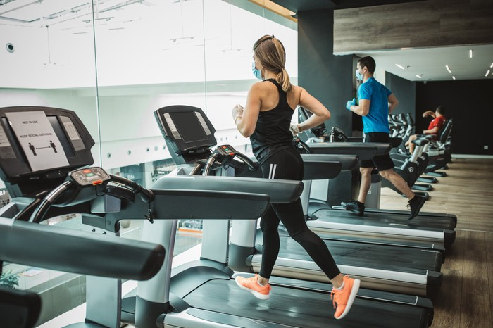 People jogging on gym treadmills while wearing face masks.