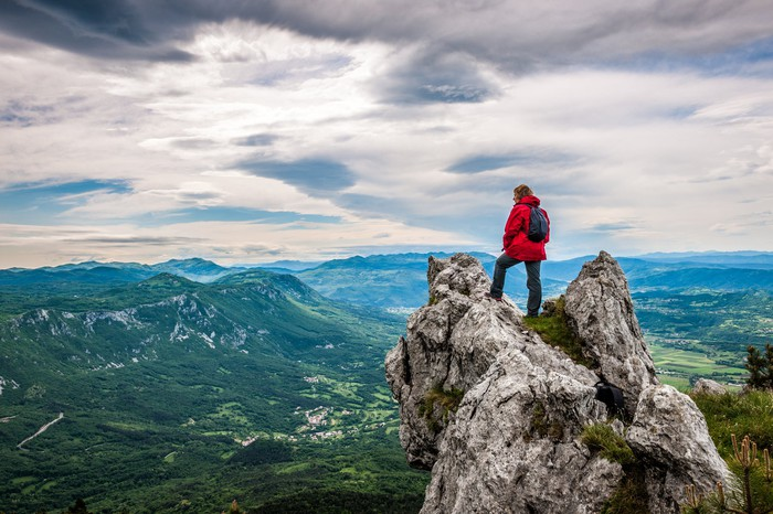 A woman stands on a mountain top and looks out over the landscape.