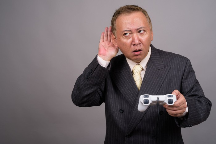 A businessperson holding a video game controller cups his ear and glances sideways.