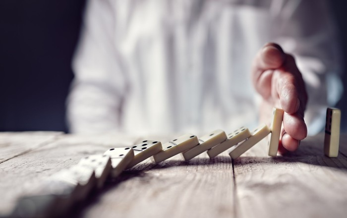 A hand stops dominoes from falling.
