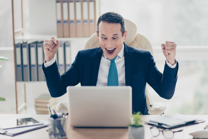 Man at laptop smiling and excitedly raising arms