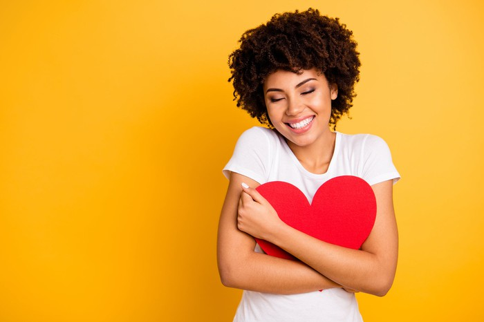 A young woman is embracing a red cardboard heart and smiling.