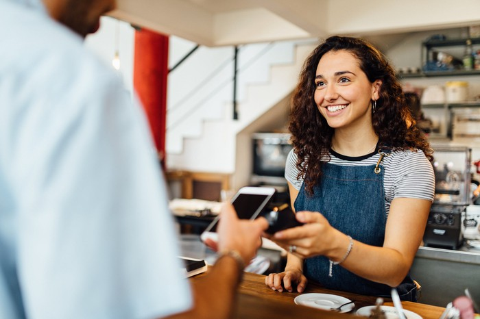 Woman at a store with a customer paying with a contactless payment.