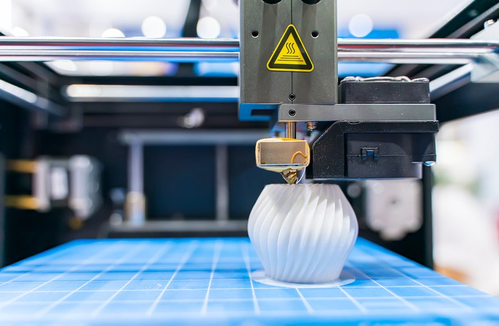 Close-up of a 3D printing producing a white plastic object on a blue surface.