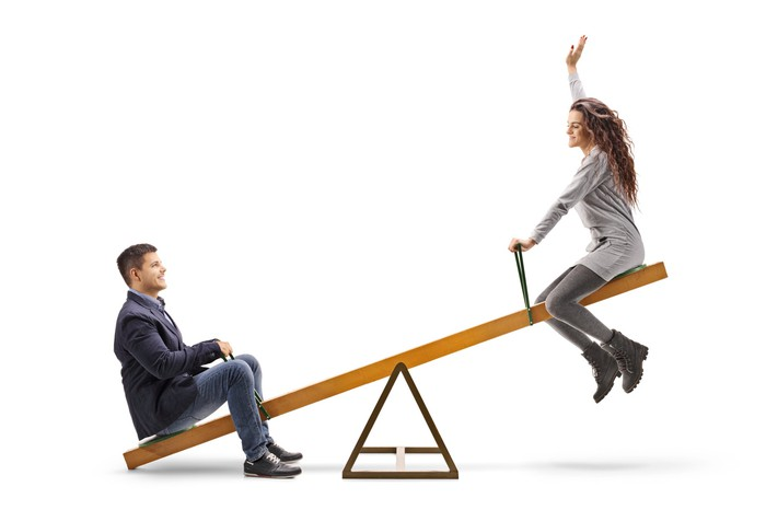 A man and a woman on a seesaw.