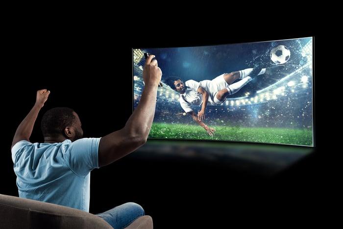 man cheering streaming soccer on big screen tv
