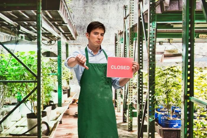 Un agriculteur de marijuana exprime son mécontentement face à la fermeture de son entreprise avec un pouce vers le bas et un panneau indiquant fermé.
