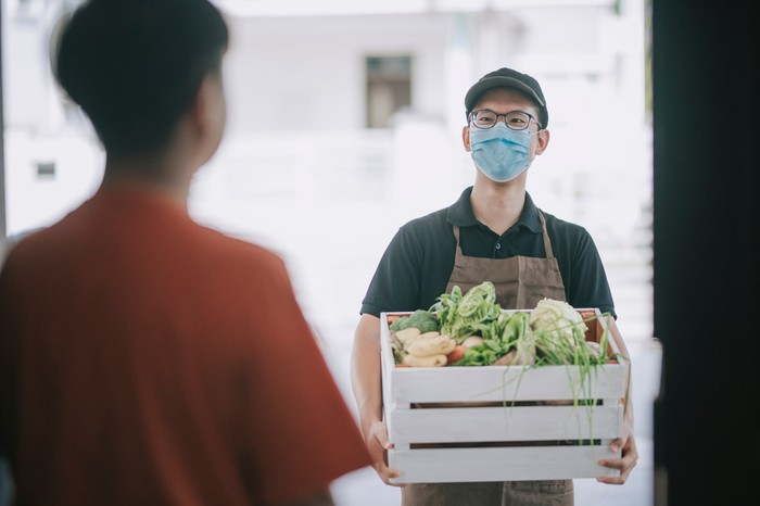 A masked delivery man stands outside an open front door with a crate of vegetables.