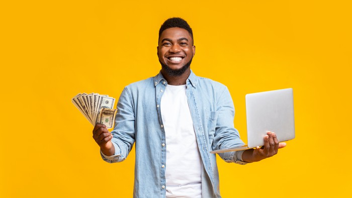 Man holding cash and laptop.