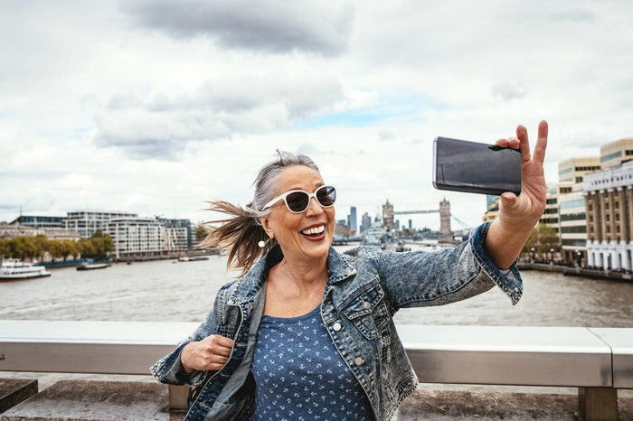 A middle aged woman take s a selfie with London Bridge in the background.