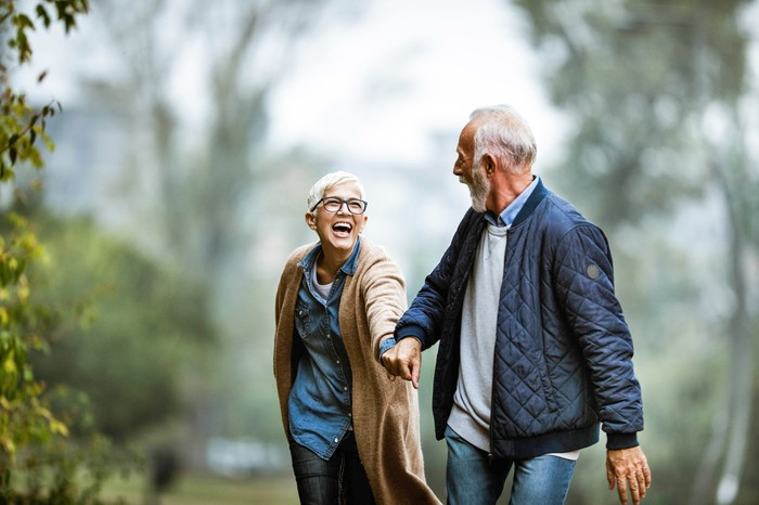 Smiling retiree couple holding hands and walking outside