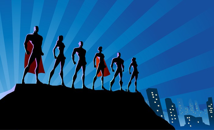 Silhouettes of six male and female superheros standing on a ledge in front of a city at night.