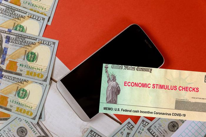 Economic stimulus check next to smartphone and $100 bills