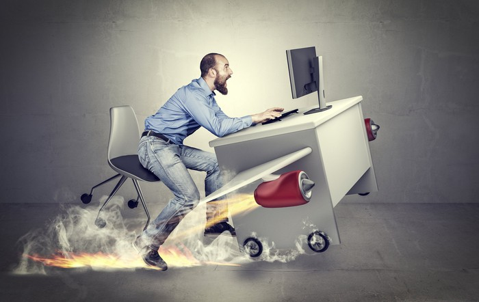 An office worker holds on to his desk as it takes off on a rocket-powered flight.