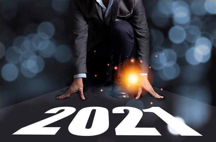 "An investor kneels as if to run a race with the year ""2021"" written at his feet."