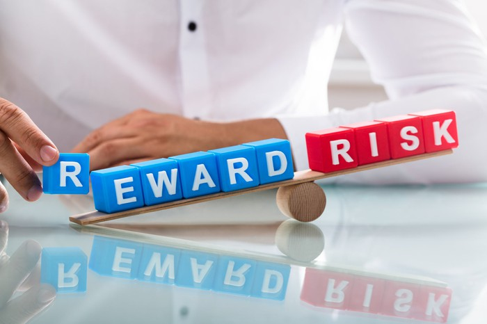 A balance with the words risk and reward on it spelled out with blocks.