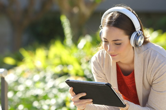 Woman holding a tablet and wearing headphones.
