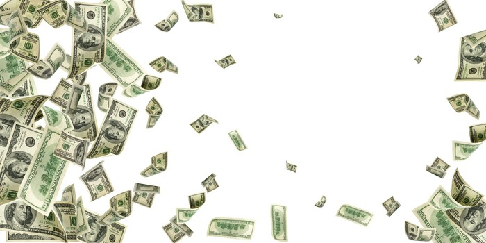 A large number of 100 dollar bills floating in the air in front of a white background