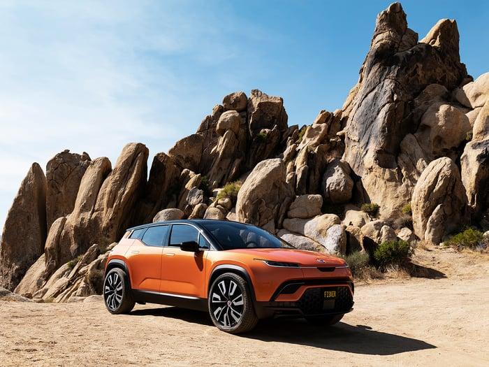 Orange Fisker Ocean SUV in a desert landscape.