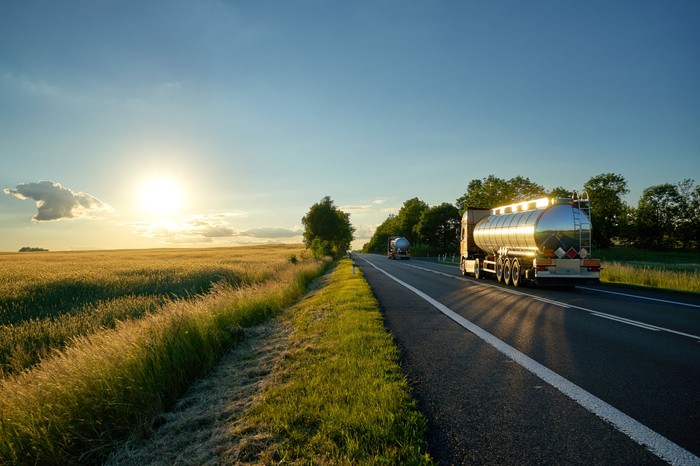 Fuel trucks heading towards the sunset on a country road.