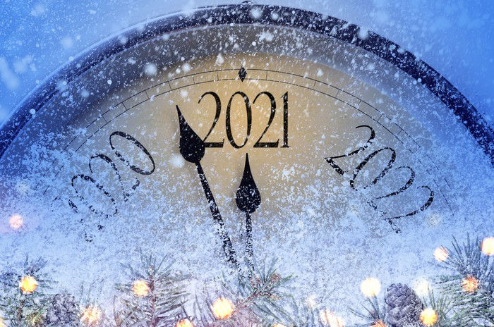 A giant clock, face mostly frosted, with hands moving to 2021