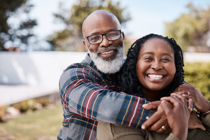 Smiling senior man and woman embracing