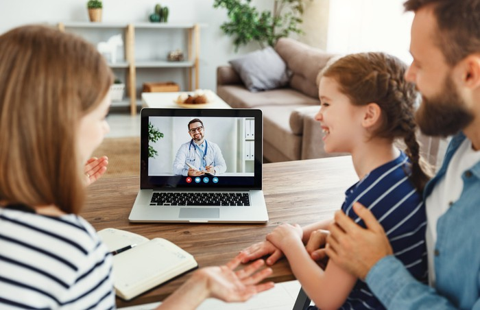 Two adults and child video conferencing with doctor