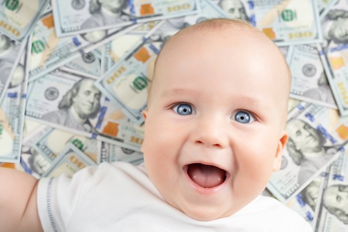 A baby lies on a pile of cash.