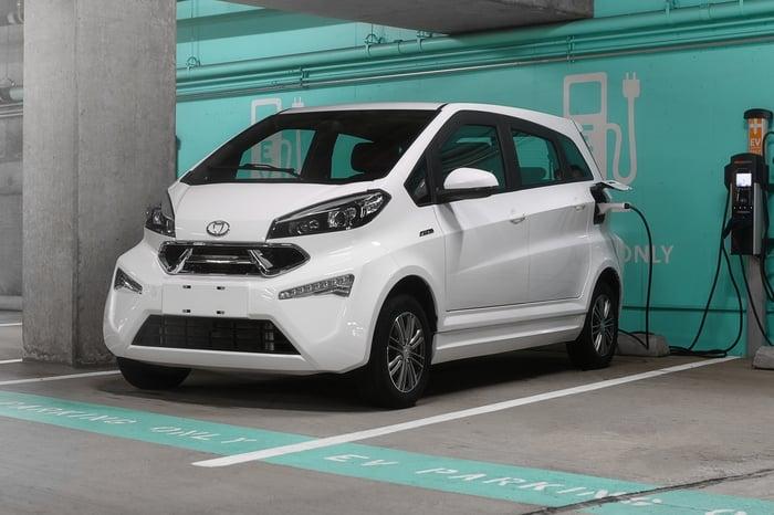 white Kandi model K23 being charged in parking  garage