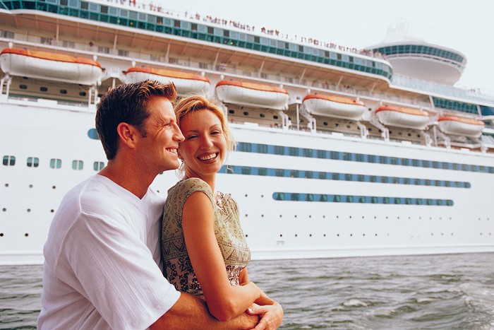 A couple poses in front of a cruise ship at port.