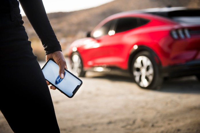 A woman holding a cell phone with a Ford logo faces a red Ford Mustang Mach-E in the background.