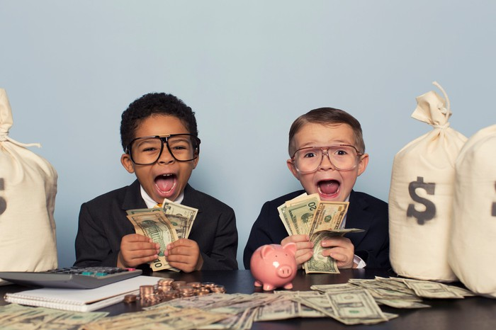 Two children dressed in suits make excited faces while holding up cash.