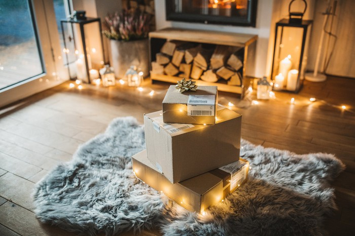 Pile of mail packages on rug surrounded by string lights. Fireplace and lit candles in the background.