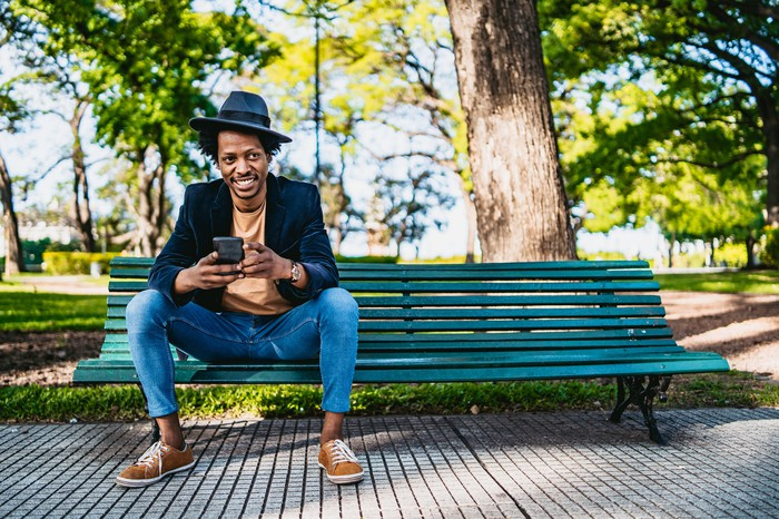 A smiling man sits on a park bench with his phone.