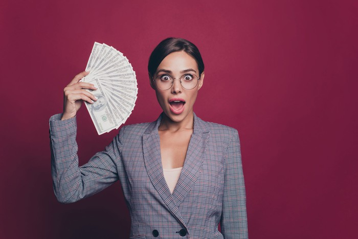 A woman holding up a fan of money.