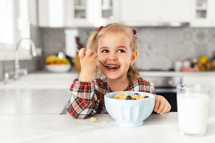 A young, smiling girl eating cereal at a white kitchen counter.